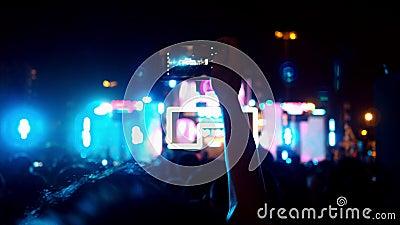 Manos de la gente de la muchedumbre de la audiencia que toma la foto con concierto elegante móvil del teléfono en festival de mús almacen de metraje de vídeo