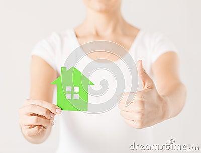 Manos de la mujer que sostienen la casa verde