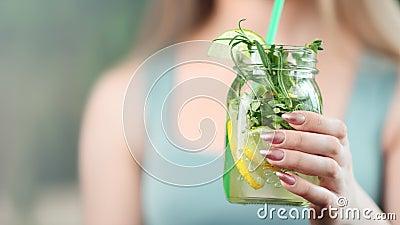 Manos del primer de la mujer joven que dan a refresco el cóctel sano con la rebanada de limón y de menta metrajes
