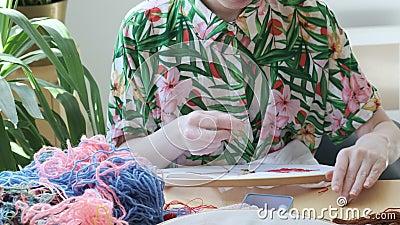 Manos femeninas cosiendo con aguja capucha bordada, tela con imagen colorida almacen de metraje de vídeo