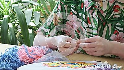 Manos femeninas cosiendo con aguja capucha bordada, tela con imagen colorida almacen de video