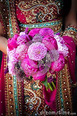 Manos indias de las novias que sostienen el ramo