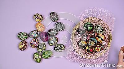 Manos poniendo canasta de huevos de Pascua cerca de la canasta sobre fondo rosa La Pascua es sagrada 4 kK almacen de video
