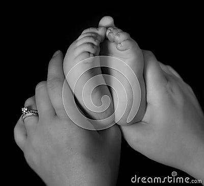 Manos que llevan a cabo pies infantiles en blanco y negro