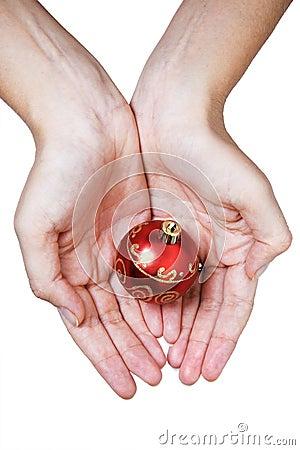 Manos y chuchería roja de la Navidad