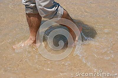 Mans feet in the sea