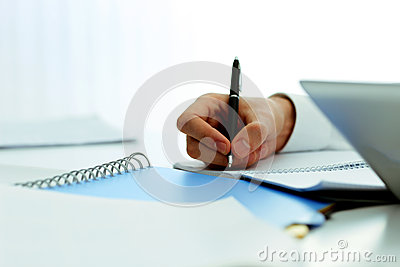 Mans hand writing in notebook