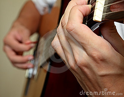 Mans  hands playing guitar