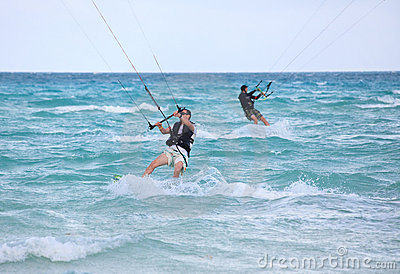 Mans riding his kiteboard.