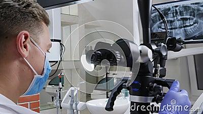 Manspecialisten arbetar med det optiska mikroskopet som är främst av käken på bildskärm i kontor för tandläkare` s arkivfilmer