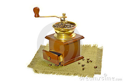 Manual coffee-grinder and coffee beans on canvas.