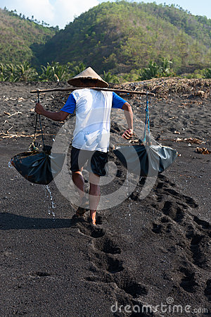 Traditional sea salt production on on the volcanic black sand, B Editorial Photo