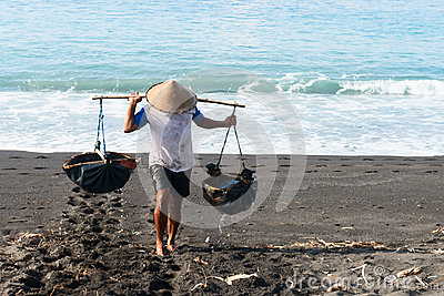 Traditional sea salt production on the volcanic black sand, Bali Editorial Stock Image