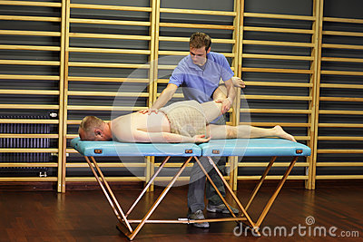 Manual therapist working with man s leg and back