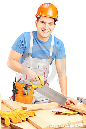 Manual worker with helmet cutting wooden batten with a saw