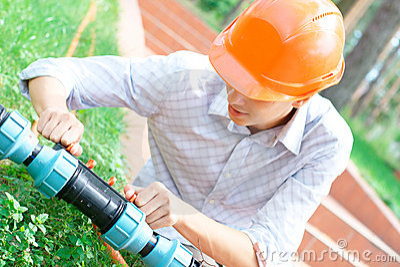 Manual worker repairing a pipe