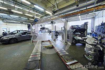 Many cars stand in car garage with special equipment