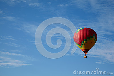 Many-colored hot air balloon with people fly