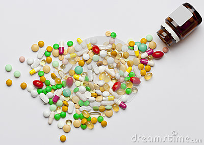 Many colorful medicines spilling out of a bottle.