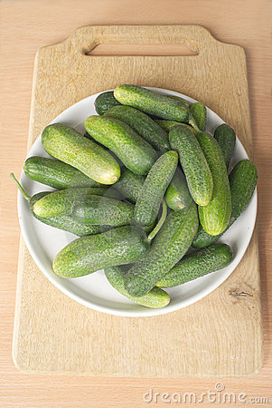 Many green cucumbers on brown cutting board re