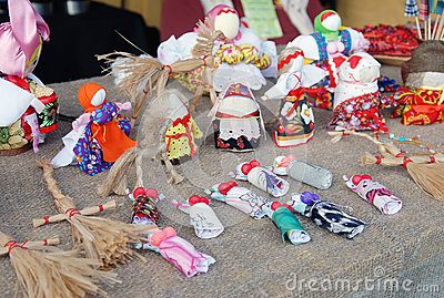 Many handmade dolls on the table.