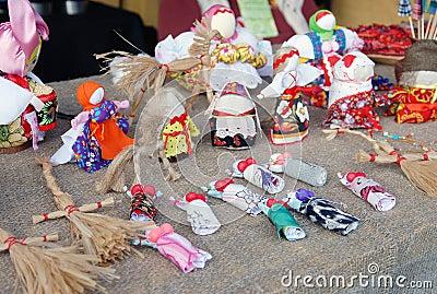 Many handmade dolls on the table.