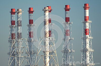 Many high industrial smoke pipes on blue sky