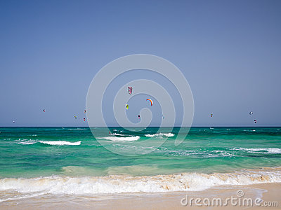 Many kites over green ocean waves