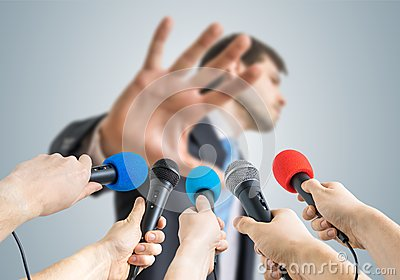 Many reporters are recording with microphones a politician who shows no comment gesture Stock Photo