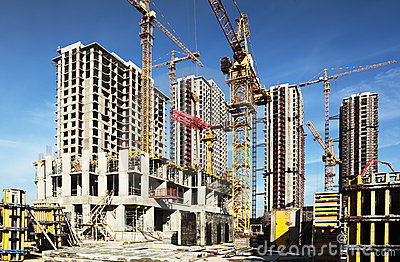 Many tall buildings under construction and cranes