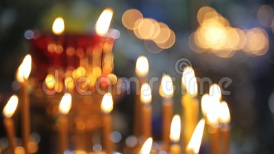 Many wax yellow candles brightly burn in church. stock video footage