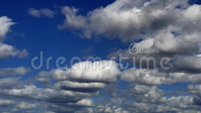 Many white clouds move by blue sky at sunny day. Time lapse stock footage