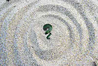 Maori koru fern green stone on sand