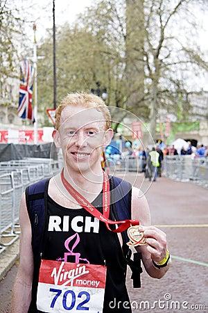 Marathon runner showing his olimpic meda; Editorial Image