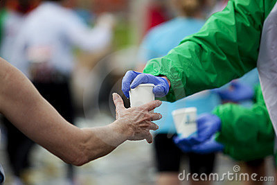 Marathon runner taking cup of water at the refresm