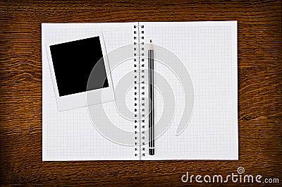 Marco de la foto en el cuaderno en blanco con el lápiz