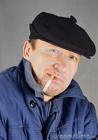 Marginal man in a cap with a cigarette