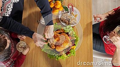Marido corta frango sentado à mesa do jantar na véspera de Ano Novo filme