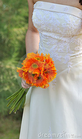 Mariée dans la robe de mariage blanche avec le bouquet
