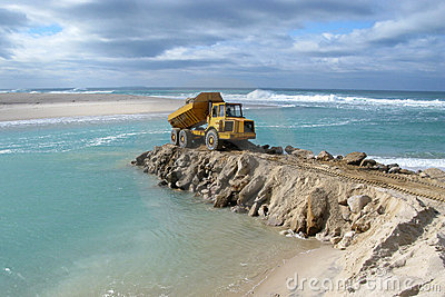 Marine construction. truck dumping rocks at sea