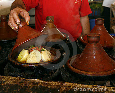 Market cook holding a cover of a tajine, Morocco