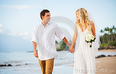 Married couple, bride and groom holding hands at sunset on beaut