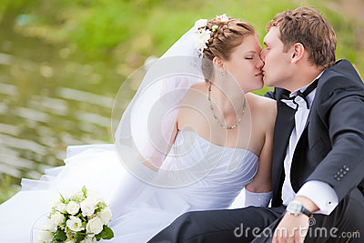 Married couple kissing in park