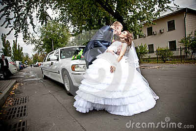 Married couple kissing on road in front of car