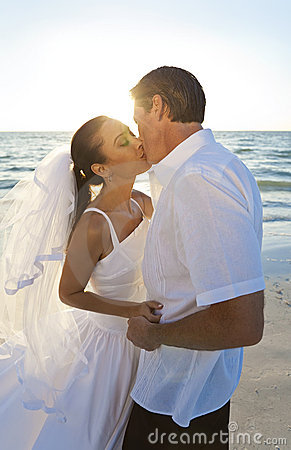 Married Couple Kissing at Sunset Beach Wedding