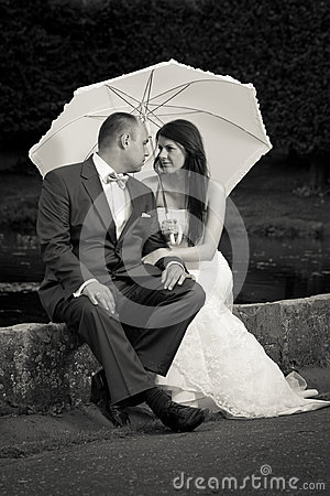 Married couple in the park with white umbrella