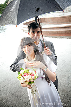 Married couple standing under umbrella