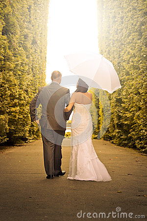 Married couple walking in the park with umbrella