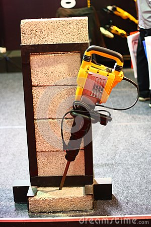 Marteau jaune de démolition cassant la démonstration de brique