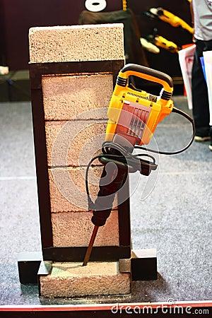 Martelo amarelo da demolição que quebra o programa demonstrativo do tijolo